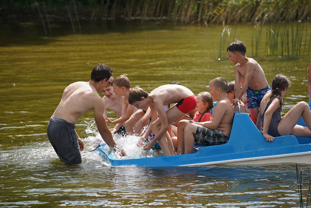Boys and girls in a boat, laughing, splashing water