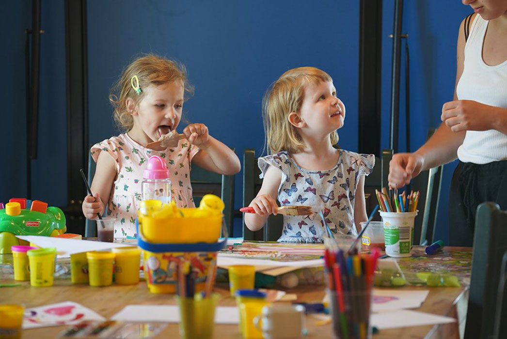 Two young girls playing with paint and bright colours