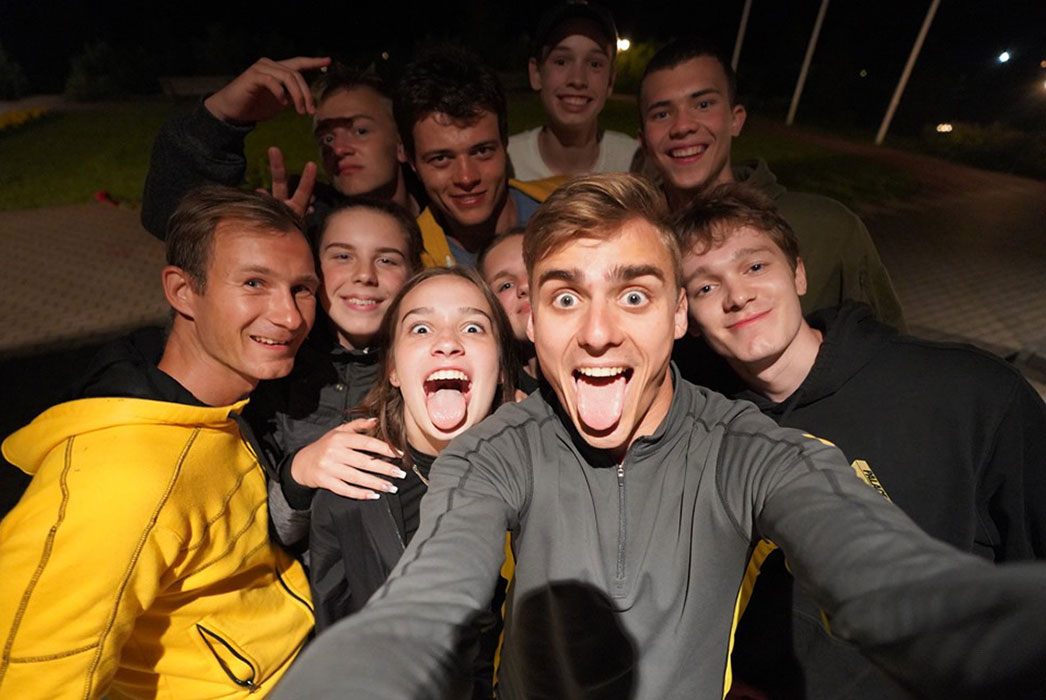 Selfie of 10 young men and women, smiling in the dark, flash from the camera