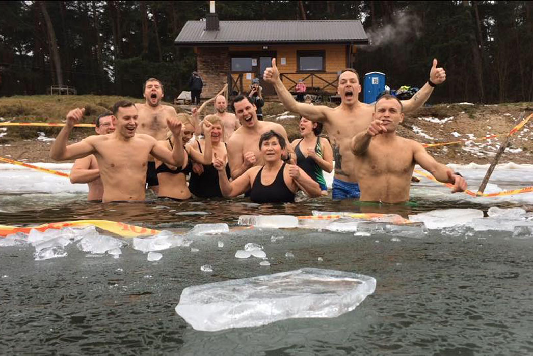 Eleven men and women standing waist high in water, laughing, shouting, surrounded by floating ice!